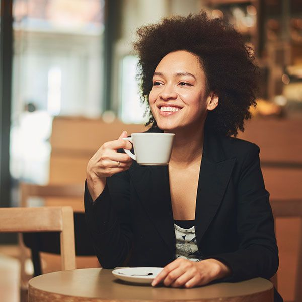 Woman at coffee shop smiling and holding coffee cup