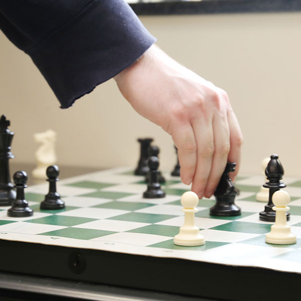Hand moving a chess piece on a chess board