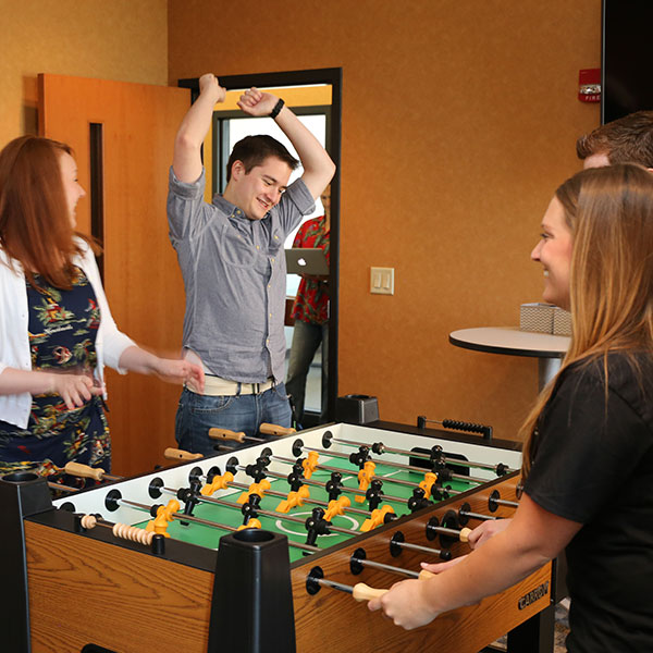 Teammates playing foosball and smiling