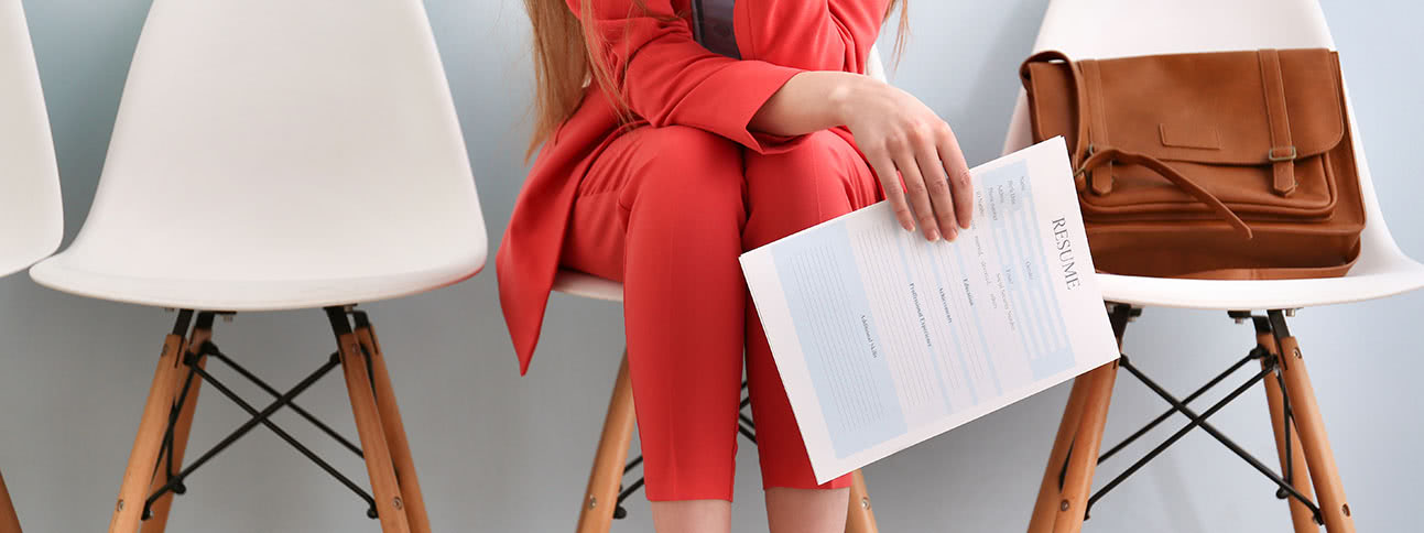 Woman in suit sits with resume in-hand