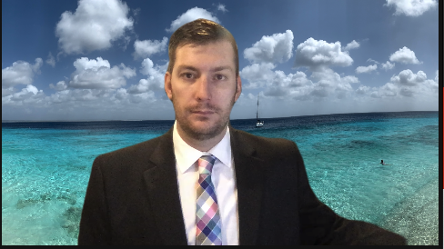 Kevin joining a meeting in a suit and tie with a beachfront Zoom background.