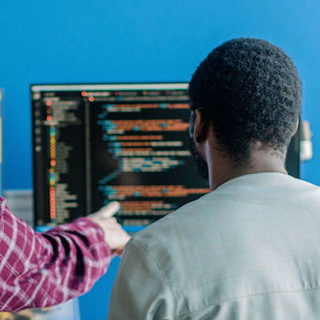 two teammates pairing at a work station looking at code
