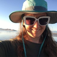 A selfie of Lara smiling at Great Salt Lake wearing a sunhat and dark sunglasses