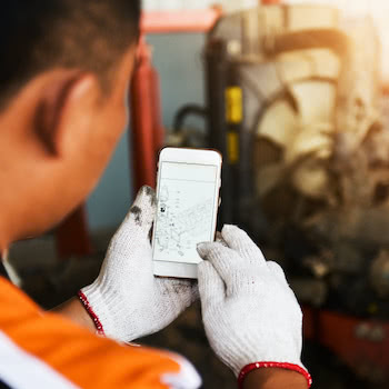 industrial worker looking at schematic plans on his phone in a factory setting