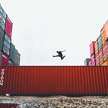 man jumping over shipping container