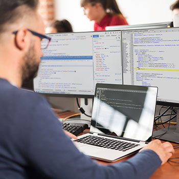 A bearded person wearing glasses writing code in light mode with other teammates in the background