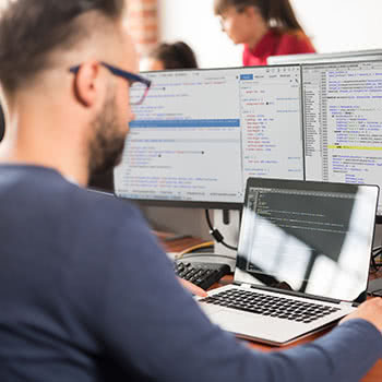 Man looks at code on laptop with dual-monitors